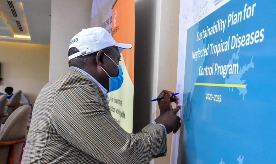 A representative from Uganda's Ministry of Education signs Uganda's sustainability plan for NTDs at the launch event on February 4, 2021