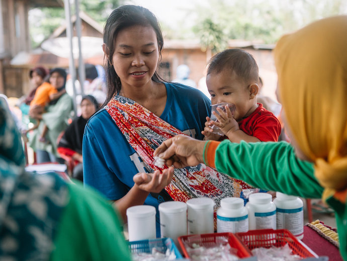 A woman and child receive medicine during an MDA in Indonesia