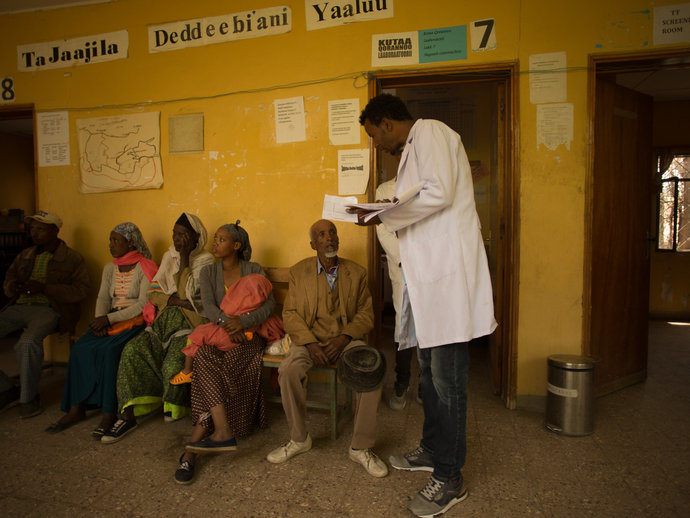 A healthworker stands in the middle of a clinic.
