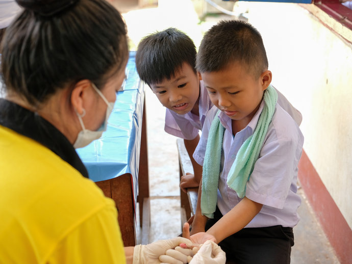 A young boy has his finger pricked during a survey for lymphatic filariasis.