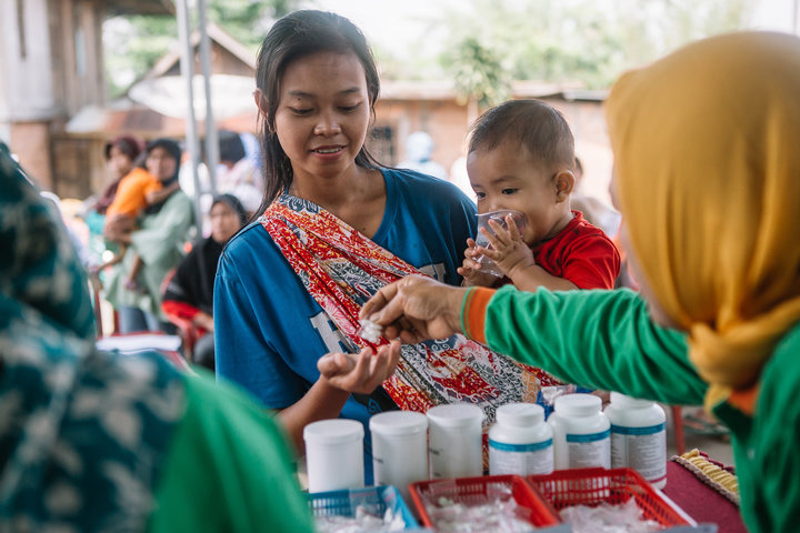 A woman and child receive treatment during an MDA in Indonesia