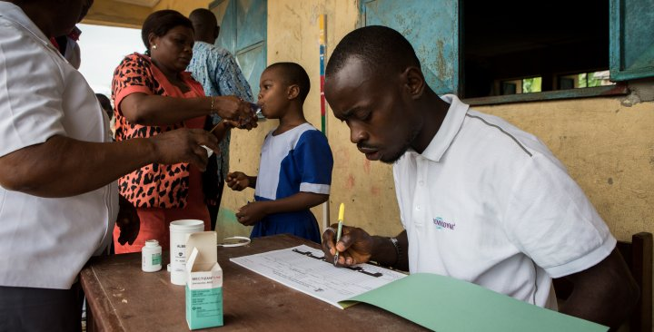 A health worker enters treatment data during a school-based NTD campaign