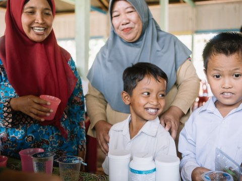 Students in Indonesia receive medicine during the national NTD campaign.