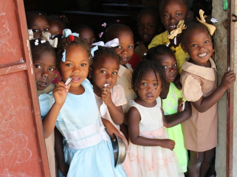Haitian schoolchildren gather by the door during an NTD survey.