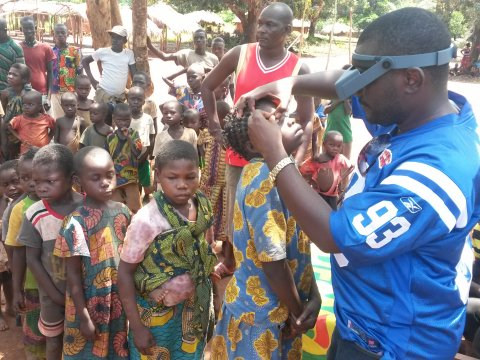 Children queue to have their eyes examined for trachoma in DRC.
