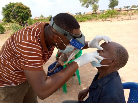 A surveyor in DRC uses the integrated loupe-shield to examine a man's eyes for trachoma.