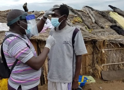 A surveyor in DRC uses the loupe-shield to examine a man's eyes for trachoma.