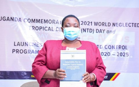 Hon. Minister of State for Health, Hon. Rhobinah Nabbanja shows Uganda's newly launched sustainability plan for NTDs at the launch on February 4, 2020.