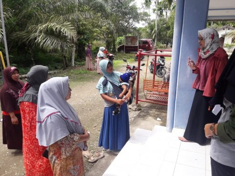 Wita Larasati explains LF medicines to breastfeeding woman during an NTD campaign in Indonesia.